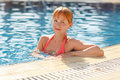 Charming slender red-haired girl in a swimsuit at the pool in th