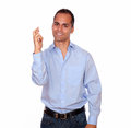 Charming smiling adult man crossing his fingers portrait of a and looking at you on isolated background Royalty Free Stock Images