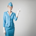 Charming stewardess in blue uniform pointing the finger dressed on gray background Stock Photos