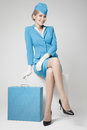 Charming stewardess in blue uniform and suitcase on gray dressed background Royalty Free Stock Images