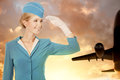 Charming stewardess dressed in blue uniform on sky background with plane Royalty Free Stock Photo