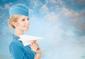 Charming stewardess holding paper plane in hand blue sky backgr on background Royalty Free Stock Image