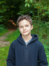 Charming teenage boy standing in a forest looking into the camera Royalty Free Stock Images