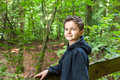 Charming teenage boy standing in a forest looking into the camera Stock Photography