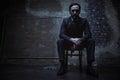Charming villain sitting in dark room