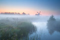Charming windmill by misty river at sunrise groningen netherlands Royalty Free Stock Image