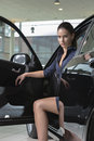 Charming woman in the car beautiful model sitting fancy with door open looking straight to camera indoors background Stock Photography