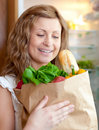 Charming woman holding a grocery bag Stock Images