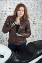 Charming woman unzips vintage brown leather jacket while standing near motorbike in garage, brick wall background Royalty Free Stock Photo