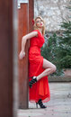 Charming young blonde in red sexy dress with red flower in hair posing against wooden wall.Sensual gorgeous young woman Royalty Free Stock Photo