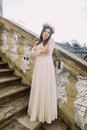 Charming young bride in long white wedding dress and floral wreath standing back on the old stone stairs Royalty Free Stock Photo