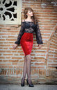 Charming young brunette woman in black lace blouse red skirt and high heels near the brick wall sexy gorgeous young woman old Stock Photography