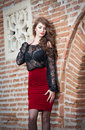 Charming young brunette woman in black lace blouse red skirt and high heels near the brick wall sexy gorgeous young woman old Stock Images