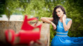 Charming young brunette woman in bright blue dress with red shoes in foreground. gorgeous fashionable woman, outdoor shot Royalty Free Stock Photo