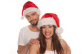 Charming young couple in red santa hats standing close together smiling at the camera as they celebrate christmas isolated on Stock Photos