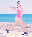 Charming young female exercising on exercise mat outdoor