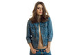 Charming young girl with beautiful hair posing for the camera in a jeans jacket