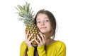 Charming young girl presses to face large ripe pineapple. Royalty Free Stock Photo
