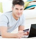 Charming young man with card and laptop lying Royalty Free Stock Image