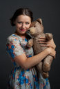 Charming young woman holding teddy bear a in colorful dress is studio photo on gray background Royalty Free Stock Image