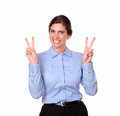 Charming young woman standing with victory sign a portrait of a on blue blouse on isolated background Royalty Free Stock Image