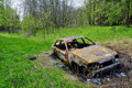 Charred car in the woods Royalty Free Stock Images