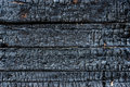 Charred wood black with rusty nails in it Stock Image