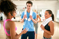 Chat between exercisers after fitness training young men and two women while resting at gym Royalty Free Stock Image