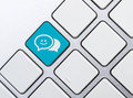 Chat social network concept balloon icon blue button or key on white keyboard Stock Image