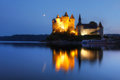 Chateau de val france in auvergne at twilight with crescent moon mirroring in the still waters of the artificial lake surrounding Royalty Free Stock Photography