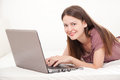 Chatting young woman lying on bed and using laptop on white background Royalty Free Stock Photos