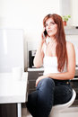 Chatty in the kitchen a young adult woman sitting while talking on a smartphone Royalty Free Stock Photo