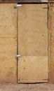 Cheap door a made out of thin wood planks locked from the left side Royalty Free Stock Photo