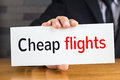 Cheap flights, message on white card and hold by Royalty Free Stock Photo