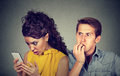 Cheating boyfriend. Man nervously biting fingernails while shocked girlfriend reading text messages on his mobile phone Royalty Free Stock Photo