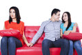 Cheating in partnership beautiful young women holding hands with men sitting near his girlfriend Royalty Free Stock Photography