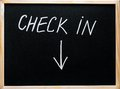 Check in message and arrow pointing downwards written with white chalk on wooden frame blackboard Royalty Free Stock Photography