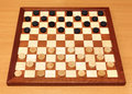 Checkerboard with checkers spaced wooden on table Stock Photo