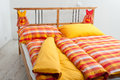 Checkered bedding in interior of bedroom red orange and yellow Stock Images