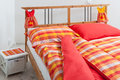 Checkered bedding in interior of bedroom red orange and yellow Royalty Free Stock Photography