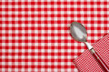 Checkered table cloth with red and white checks and a spoon napkin on Stock Image