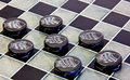 Checkers pieces game made ​​of ceramic on a game board Royalty Free Stock Photography