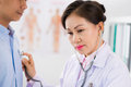 Checking heartbeat mature vietnamese doctor listening to of her male patient Royalty Free Stock Photo