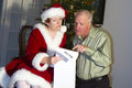 Checking it twice man reacting with happy surprise when mrs claus shows him santa s list Royalty Free Stock Photos