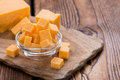Cheddar pieces of close up shot on an old wooden table Royalty Free Stock Photos