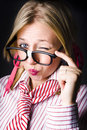 Cheeky female business geek showing naughty wink pink pout whilst pulling down glasses depiction business trickery Royalty Free Stock Photo