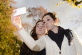 Cheeky sisters with smartphone in autumn park Royalty Free Stock Photos