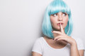 Cheeky young girl in modern futuristic style with blue wig thinking over white Royalty Free Stock Photo