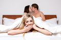 Cheeky young woman in a threesome in bed women or the cheating partner an affair peeking out of the bottom of the bedclothes with Royalty Free Stock Image