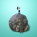 Cheered businessman climb on top of large rock in green background Royalty Free Stock Photos